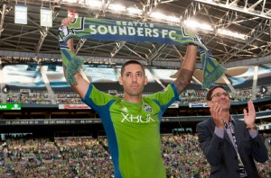 Clint Dempsey raises the Sounders FC scarf at last Saturday's match as Adrian Hanauer looks on.