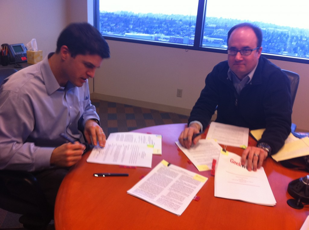 Attorney David Wickwire of WSGR signing papers with GeekWire's Todd Bishop
