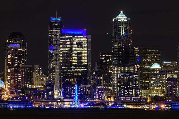 """The Seattle skyline bathed in blue, in honor of Paul Allen, from the Great Wheel on the waterfront to """"PA"""" on the Russell Investments Center."""