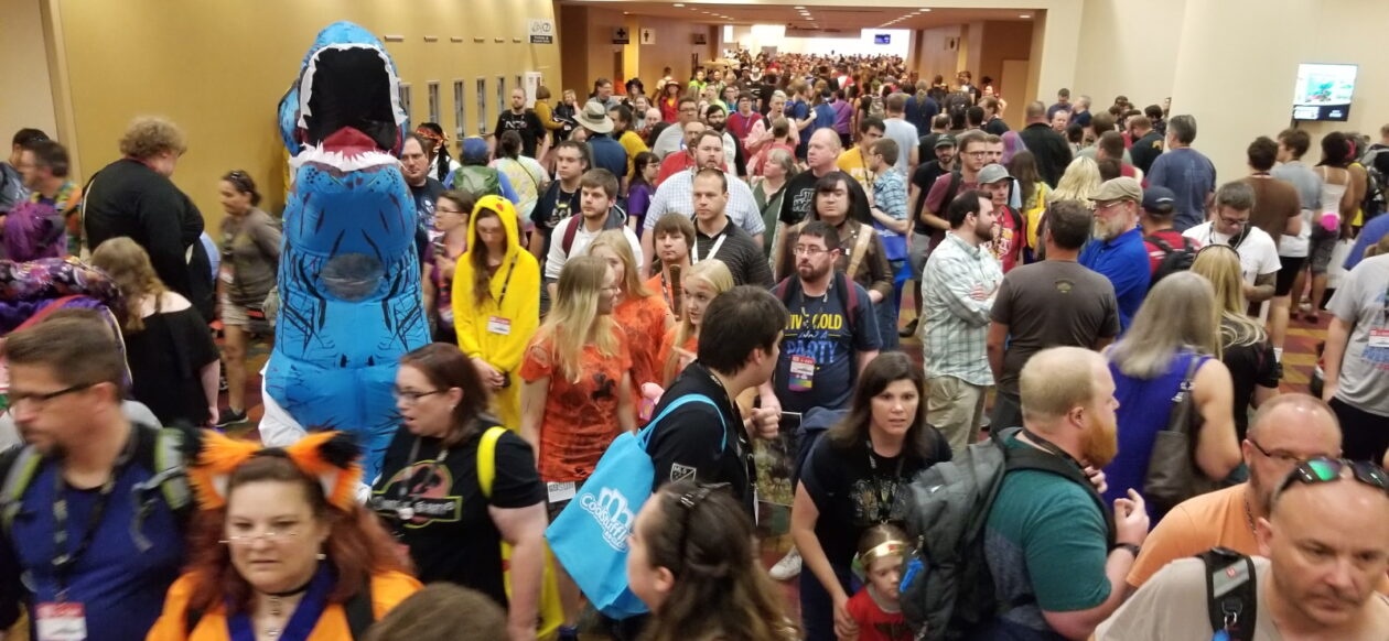 A crowded hallway at Gen Con. Also a blue t-rex.