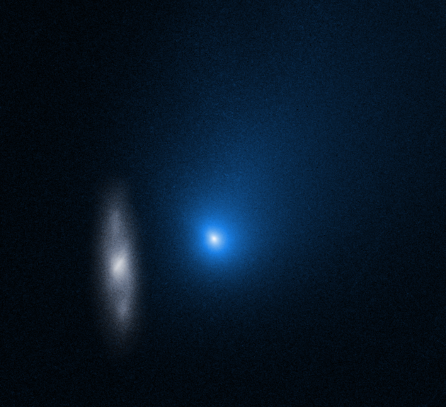 Hubble image shows distant galaxy photobombing an interstellar comet as it swings around the sun